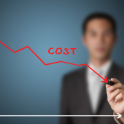 Man behind a graph drawing a line downward that says cost